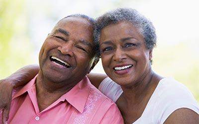 senior couple smiling after receiving restorative dental care