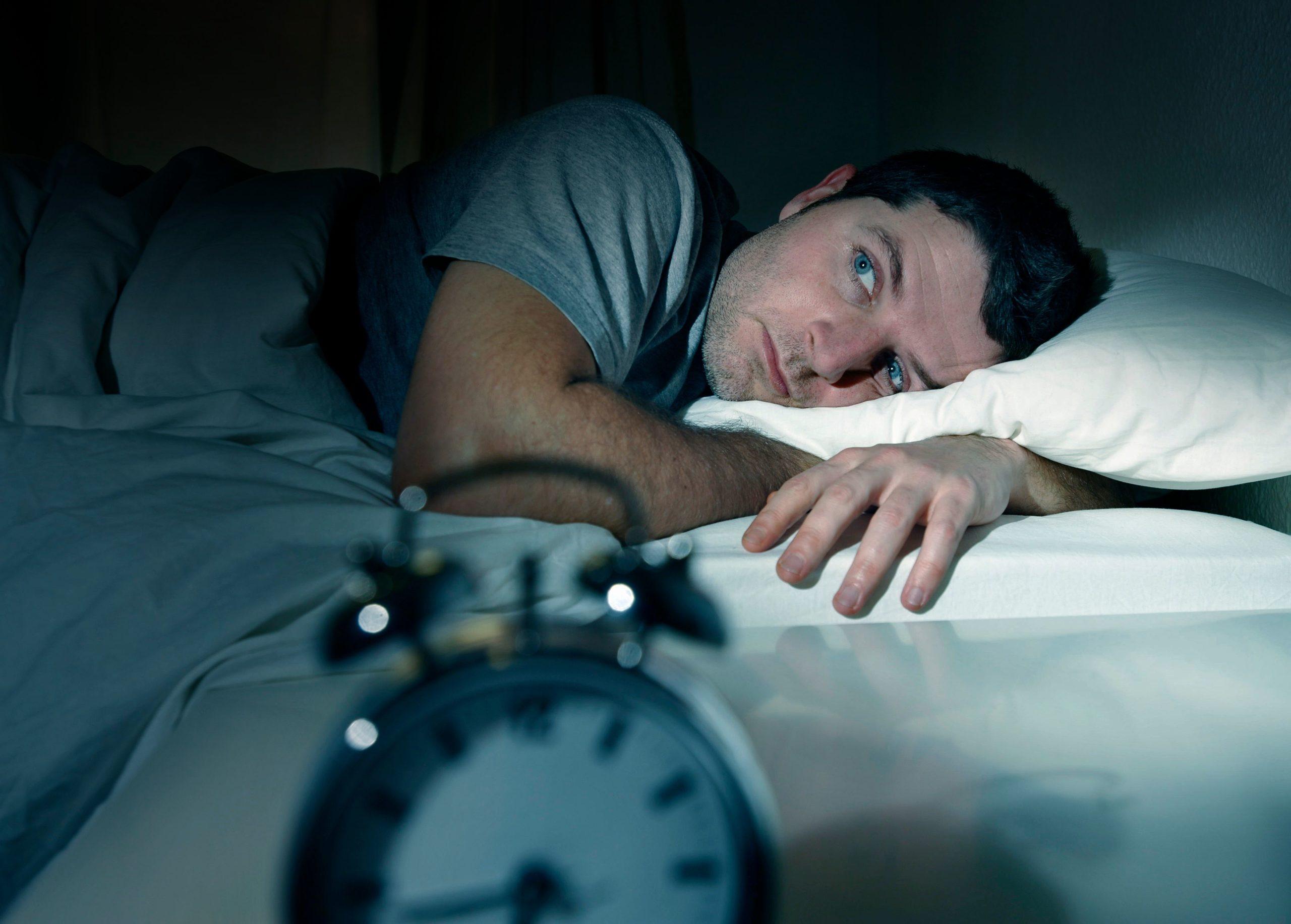 man laying awake at night from sleep apnea